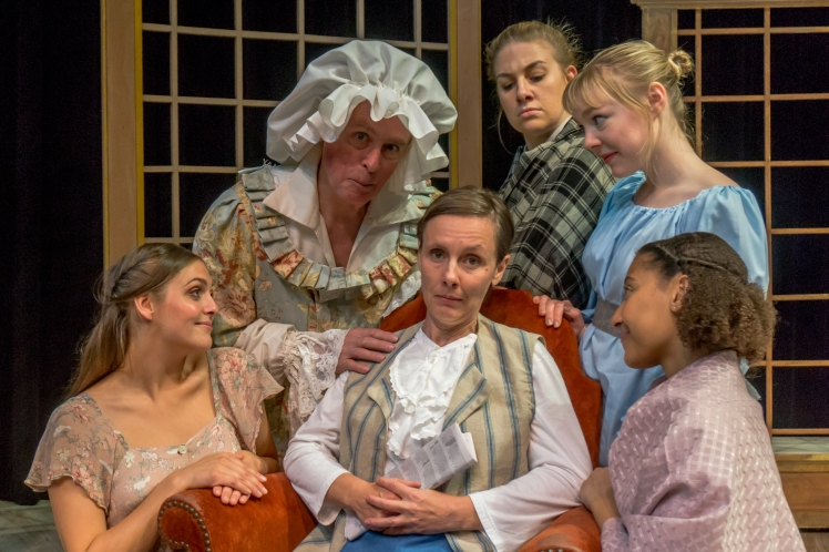 A cast photo from Lost Nation Theater's production of Pride & Prejudice. The patriarch of the Bennet family is seated, surrounded by his wife and four daughters.